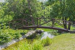 夏天小径在有一座桥梁的城市公园在一个晴天 免版税库存图片