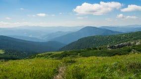 夏天山、绿草和蓝天风景 库存图片