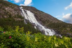 夏天山在倾斜Etne,挪威的Langfossen瀑布 库存照片