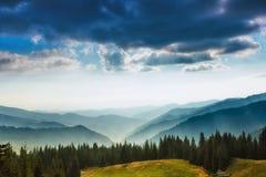 夏天山庄严风景  山的有薄雾的倾斜的看法在距离的 库存图片