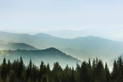夏天山庄严风景  山的有薄雾的倾斜的看法在距离的 免版税库存图片