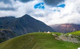 夏天山绿草和蓝天环境美化 旅游阵营 黑暗的峰顶 放松的一个巨大地方 Gudauri 免版税库存照片