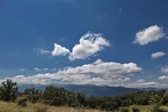 夏天山绿草和蓝天与云彩 免版税库存图片