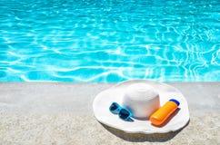 夏天帽子、太阳镜和遮光剂在水池附近 库存图片