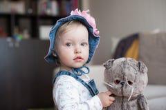 夏天帽子的严肃的女婴 有一朵大桃红色花的巴拿马 库存图片
