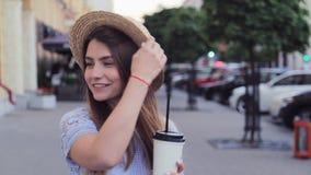夏天帽子的俏丽的女孩走在胡同的与拿走纸杯 股票录像