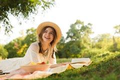 夏天帽子的可爱的少女有野餐在公园,吃果子, 免版税库存图片