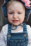 夏天帽子的哭泣的被触犯的女婴 有一朵大桃红色花的巴拿马 免版税库存图片