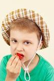 夏天帽子的小男孩吃新鲜的甜草莓的 免版税库存照片