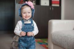 夏天帽子的微笑的愉快的女婴 有一朵大桃红色花的巴拿马 查看照相机 图库摄影
