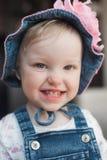 夏天帽子的微笑的愉快的女婴 有一朵大桃红色花的巴拿马 查看照相机 免版税图库摄影