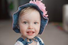 夏天帽子的微笑的愉快的女婴 有一朵大桃红色花的巴拿马 查看照相机 库存图片