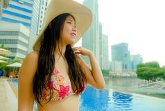 夏天帽子豪华的年轻美丽和愉快的亚裔中国旅游妇女在旅馆无限水池享用城市大厦的观看che 免版税图库摄影