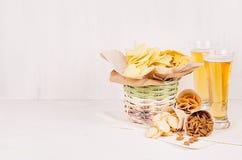 夏天快餐和储藏啤酒在玻璃-烤干酪辣味玉米片、油煎方型小面包片、芯片、玉米粉薄烙饼在土气篮子和纸角落在白色木backgr 免版税库存图片