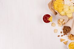 夏天快餐背景-快餐-烤干酪辣味玉米片、油煎方型小面包片、芯片、玉米粉薄烙饼在工艺纸锥体和调味汁在白木委员会 免版税库存图片