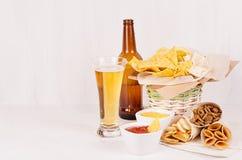 夏天快餐-不同的嘎吱咬嚼的快餐、红色和咖喱汁,在玻璃和棕色瓶的储藏啤酒在软的白木委员会 免版税库存照片