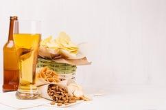 夏天快餐-烤干酪辣味玉米片、油煎方型小面包片、芯片、玉米粉薄烙饼在篮子,工艺纸角落和储藏啤酒,瓶n白色木背景 免版税图库摄影