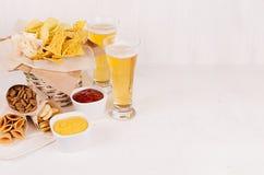 夏天快餐-不同的嘎吱咬嚼的快餐和红色,黄色调味汁在白色碗,冰镇啤酒在软的白色木板,拷贝空间 免版税图库摄影