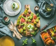 夏天或意大利食物静物画与厨房用桌、五颜六色的新鲜的切的蕃茄、无盐干酪、板材和利器 库存图片
