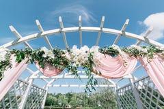 夏天户外婚礼的美丽的装饰 婚礼曲拱由轻的布料和白色和桃红色花制成在绿色 图库摄影
