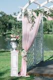 夏天户外婚礼的美丽的装饰 婚礼曲拱由轻的布料和白色和桃红色花制成在绿色 库存图片