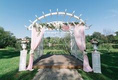 夏天户外婚礼的美丽的装饰 婚礼曲拱由轻的布料和白色和桃红色花制成在绿色 库存照片