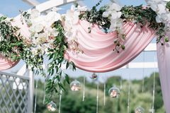 夏天户外婚礼的美丽的装饰 婚礼曲拱由轻的布料和白色和桃红色花制成在绿色 免版税库存图片