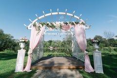 夏天户外婚礼的美丽的装饰 婚礼曲拱由轻的布料和白色和桃红色花制成在绿色 免版税图库摄影