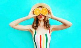 夏天拿着在她的手上两个切片橙色果子的画象妇女掩藏她的眼睛在五颜六色的蓝色的草帽 免版税库存照片