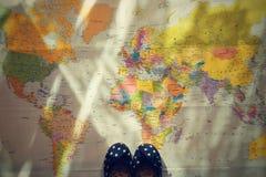 夏天旅行的美好的概念 在世界地图的小儿童的鞋子 计划一次暑假和假日 免版税库存图片
