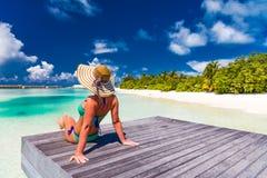 夏天旅行背景的完善的海滩假期 轻松的妇女佩带的太阳帽子和比基尼泳装在棕榈树与蓝色海 免版税库存图片