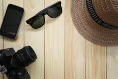夏天旅行设备、人的帽子、照相机和太阳镜在木头 免版税库存图片