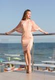 夏天旅馆` s大阳台的一个时髦的夫人 一件桃红色礼服的女孩在海附近 明亮的晴朗的背景的高夫人 库存照片