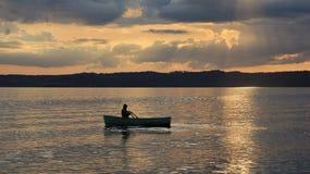 夏天日落在Ebeltoft,丹麦 在一条小船的人划船 免版税库存图片