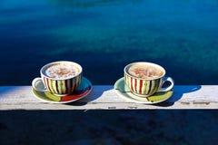 夏天早晨两个杯子热奶咖啡用在海背景的桂香 库存照片