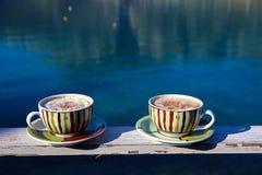 夏天早晨两个杯子热奶咖啡用在海背景的桂香 免版税库存图片