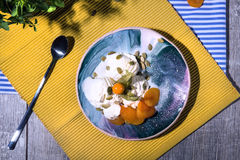 夏天早餐白色冰淇凌的顶视图用杏子和一把匙子在明亮的织品背景 冷快餐 免版税库存图片