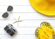 夏天时尚妇女黄色大帽子和辅助部件在海滩 热带的海运 异常的顶视图,木白色背景 免版税图库摄影