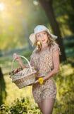 夏天时尚射击的可爱的少妇 有秸杆篮子的美丽的时兴的女孩和帽子在树附近的公园 免版税图库摄影