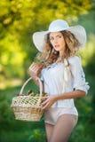 夏天时尚射击的可爱的少妇 有秸杆篮子的美丽的时兴的女孩和帽子在树附近的公园 免版税库存照片