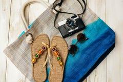 夏天时尚平的位置与照相机、拖鞋、太阳镜和其他女孩辅助部件的在白色木backgrou的袋子顶部 免版税库存图片