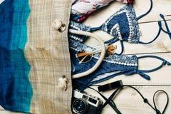 夏天时尚平的位置与蓝色比基尼泳装泳装的在袋子里面和在白色木背景的其他女孩辅助部件 库存照片