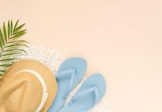 夏天时尚,在奶油色背景的夏天成套装备 白色鞋带礼服、蓝色触发器和草帽 平的位置,顶视图 免版税库存图片