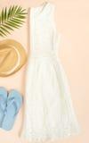 夏天时尚,在奶油色背景的夏天成套装备 白色鞋带礼服、蓝色触发器和草帽 平的位置,顶视图 库存图片