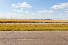 夏天有老沥青的,金黑麦领域,蓝色多云天空冒险路 库存图片