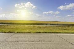 夏天有老沥青的,金黑麦领域,蓝色多云天空冒险路 库存照片