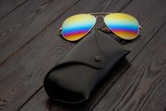 夏天有被反映的颜色透镜的飞行员太阳镜做了在金子颜色金属框架的玻璃与黑皮革盒的在a 库存照片
