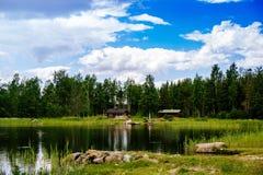 夏天村庄或原木小屋由蓝色湖在农村芬兰 库存图片