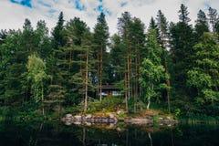 夏天村庄或原木小屋由蓝色湖在农村芬兰 免版税图库摄影