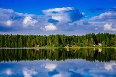 夏天村庄或原木小屋由蓝色湖在农村芬兰 图库摄影
